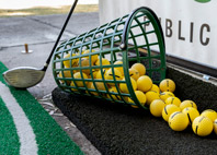 Bucket of yellow balls with a golf club leaned against the bucket