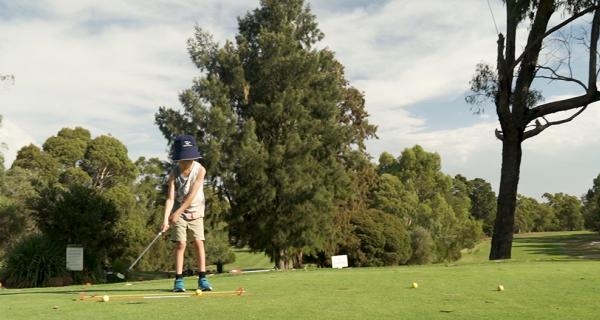 Child hitting a ball on the golf course