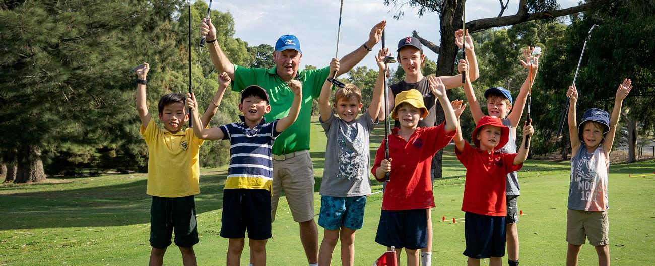 Professional golfer and students with clubs and arms in air
