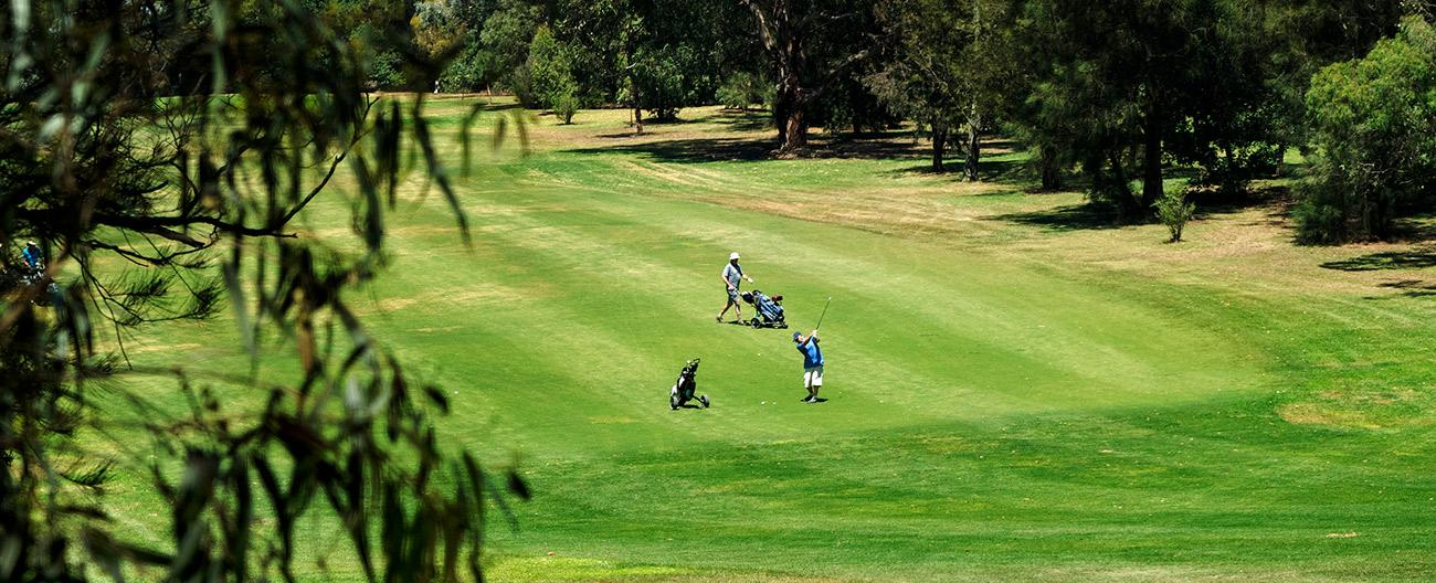 Two men playing golf on the fairway